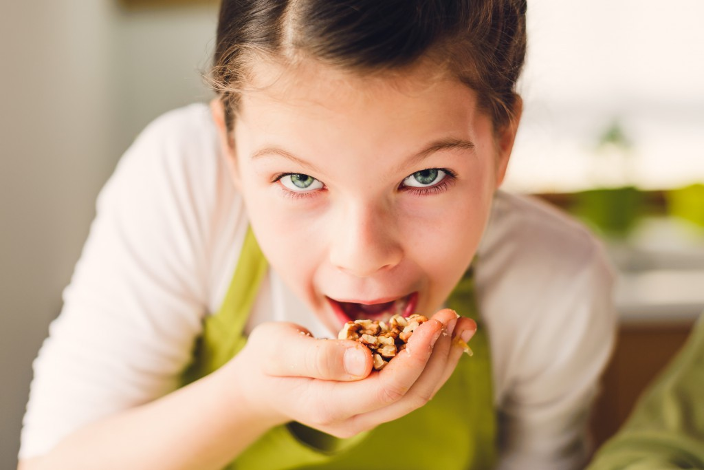 bigstock-Funny-Girl-Eating-Walnuts-116525198